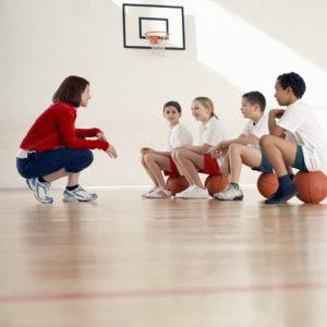 Entrenadora con equipo de baloncesto infantil mixto