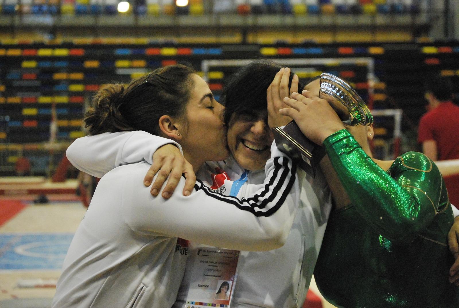 Entrenadoras de gimnasia artística abrazando a su gimnasta
