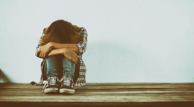 Mujer joven en posición triste abrazándose las rodillas y con la cabeza hundida